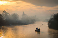 © Licensed to London News Pictures. 28/12/2016. London, UK. A narrow boat and rowers pass Hampton Court on the River Thames at first light. A very cold start to the day in some parts of the UK with temperatures well below freezing at dawn. Photo credit: Peter Macdiarmid/LNP