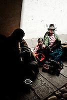 A Quechua family beg in an alleyway in Cusco, Peru