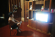 Watching TV. Surui, families, in their homes at night<br /><br />An Amazonian tribal chief Almir Narayamogo, leader of 1350 Surui Indians in Rondônia, near Cacaol, Brazil, with a $100,000 bounty on his head, is fighting for the survival of his people and their forest, and using the world's modern hi-tech tools; computers, smartphones, Google Earth and digital forestry surveillance. So far their fight has been very effective, leading to a most promising and novel result. In 2013, Almir Narayamogo, led his people to be the first and unique indigenous tribe in the world to manage their own REDD+ carbon project and sell carbon credits to the industrial world. By marketing the CO2 capacity of 250 000 hectares of their virgin forest, the forty year old Surui, has ensured the preservation, as well as a future of his community. <br /><br />In 2009, the four clans and 25 Surui villages voted in favour of a total moratorium on logging and the carbon credits project. <br /><br />They still face deforestation problems, such as illegal logging, and gold mining which causes pollution of their river systems