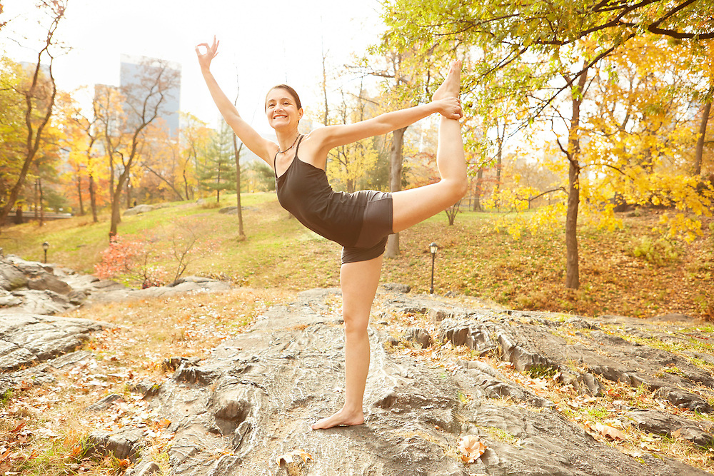 Lifestyle image of middle age woman with smile in king dancer yoga pose in Central Park New York City during Fall