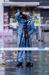 © Licensed to London News Pictures. 14/12/2020. HARROW, UK. A forensics officer takes photos of the scene in St Ann's Road. A man, believed to be in his 20s, has died and two others, believed to be in their late-teens, have been injured in a stabbing Station Road in Harrow, north west London. The Met Police said emergency services were called to the area at 19:15 GMT on Sunday 13 December to reports of a stabbing.  A crime scene remains in place.  Photo credit: Stephen Chung/LNP