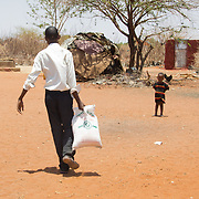 A school boy helps with the distribution of relief during the East African drought. Wajir, North Eastern Province, Kenya.