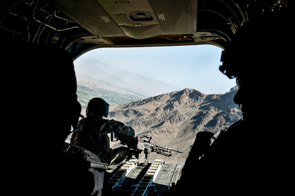A tailgunner in a U.S. Army Chinook helicopter scans the ground during a flight from Kabul to Wardak Province.