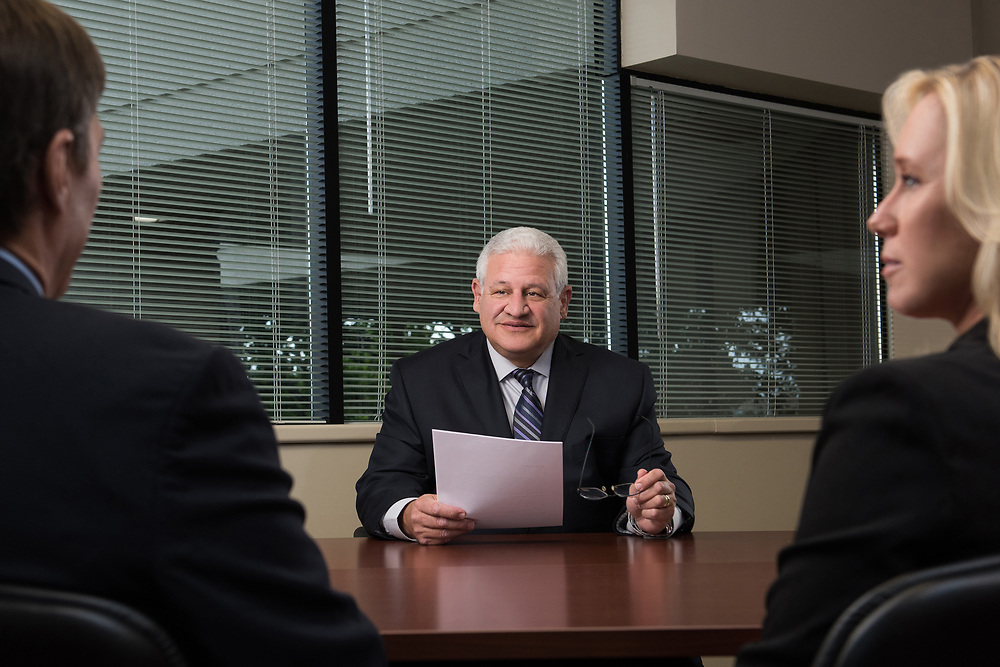 Lifestyle image of a lawyer talking with a man and a woman in a conference room.