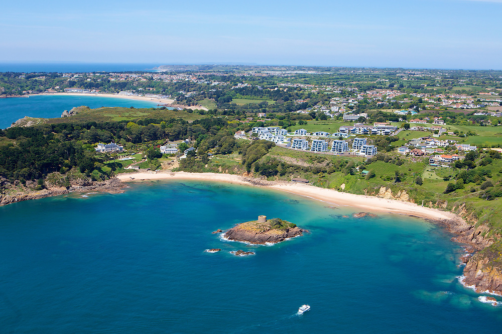 Aerial view of Portelet beach at high tide, with its cystral clear, turquoise calm water in Jersey, Channel Islands