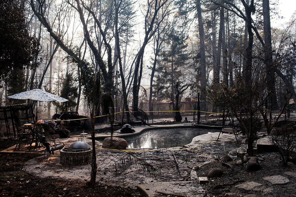 Crime tape marking the site of a found body surrounds a pool of a residential home nearby the corner of Cindy and Tabernacle lanes after the Camp Fire ripped through Paradise, California, Saturday, November 17, 2018.