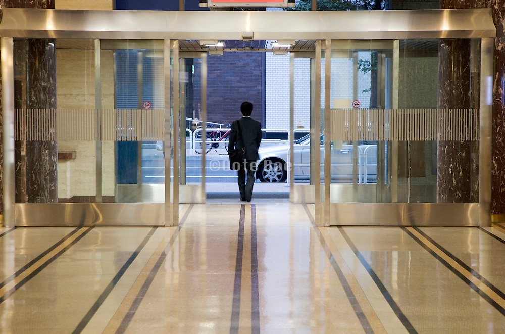 businessman walking towards the exit in a modern office building