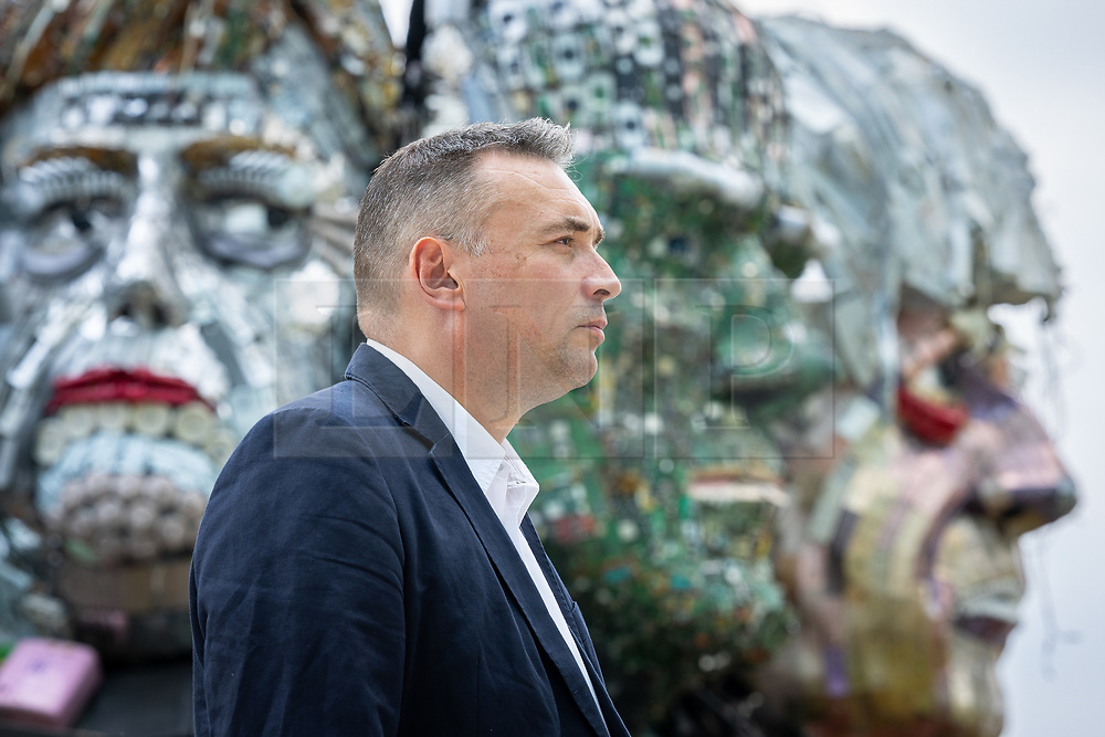 """© Licensed to London News Pictures. 21/07/2021. Stockport, UK.  musicMagpie CEO STEVE OLIVER is pictured in front of the sculpture . The E7 , a Mount Rushmore-style sculpture also known as """" Mount Recyclemore """" , is unveiled outside the Stockport headquarters of recommerce company musicMagpie , who commissioned the sculpture for the G7 summit in June to much media interest . The sculpture was created out of e-waste in the likeness of the G7 leaders by artist and founder of the Mutoid Waste Company, Joe Rush , and will serve as an educational attraction during events hosted this summer , in collaboration with Totally Stockport and Stockport Council . Photo credit: Joel Goodman/LNP"""