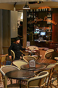 A women smokes a cigarette and has a drink at the terrace of a cafe inside Galerie Vivienne in Paris