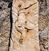 A hand lifts a boot carved in wood in the Dolomites, Val di Fassa, Italy, Europe. From Pera di Fassa village (in Pozza di Fassa comune in Val di Fassa), in Trentino-Alto Adige/Südtirol region, Italy, take a bus or lift to visit Rifugio Gardeccia Hutte and hike in the Rosengarten mountain massif (Catinaccio Group) of the Dolomites. UNESCO honored the Dolomites as a natural World Heritage Site in 2009.