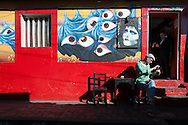 """The Colombian capital has a youthful and informal, mural art is widespread and the central area called Candelaria has is historical and """"bohemian"""" side much appreciated by tourism backpacker and youth local student. <br /> A tourist enjoys a sunburst and a good local beer in one of the bars of the """"Callejon embudo."""""""