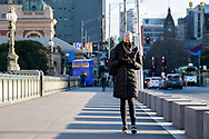 A woman in a mask crosses Princess Bridge as the state waits to see if the lockdown will be extended as it enters 6th day of the state wide COVID-19 snap lockdown that has been placed on the State of Victoria.  (Photo by Michael Currie/Speed Media)