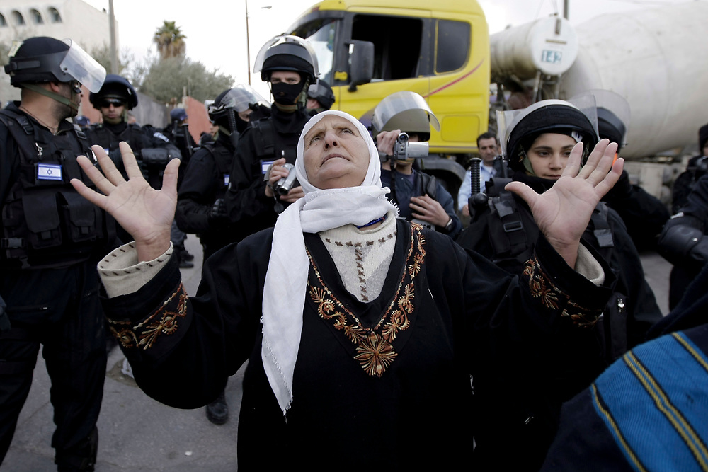A Palestinian woman reacts near Israeli police officers<br /> while contractors working for the Israeli police department seal off entrances to the house (unseen) of a Palestinian man who attacked the Mercaz Harav Yeshiva, a Jewish religious seminary in March of last year killing eight people, in east Jerusalem, on January 19, 2009.