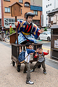 Children mimic a rolling Japanese statue in a street near popular Buddhist temple Sensoji (or Asakusa Kannon Temple) in Asakusa district, Tokyo, Japan.