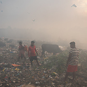 Garbage collectors in smog. A visit to one of the main garbage dump. With 15 millions population in 2019 and growing, the city of Calcutta is a typical case of expansion through uncontrolled urbanization.<br /> Calcutta, India