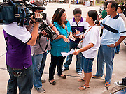 03 JULY 2011 - SAMUT PRAKAN, THAILAND:  A man and his wife who were not allowed to vote talk to Thai reporters in Samut Prakan, Thailand, Sunday, July 3. The woman said they were registered to vote but their names were not on the local voter list. More than 47,000,000 Thais were registered to vote in Sunday's election, which had turned into a referendum on the current government, led, by the Thai Democrats and the oppositionPheu Thai party. Pheu Thai is the latest political incarnation of ousted Thai Prime Minister Thaksin Shinawatra. PT is led by his youngest sister, Yingluck Shinawatra, who is the party's candidate for Prime Minister. Exit polling by three Thai polling firms showed Pheu Thai winning a landslide election.       PHOTO BY JACK KURTZ
