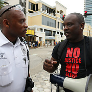 """Olumide Ajile speaks with an Orlando police officer before protesters march and hold signs in the No Justice No Peace- """"March Against Gun Violence""""  walk from Lake Eola in downtown Orlando, to the Orange County Courthouse on Wednesday, July 17, 2013. The march was organized by the Modarres Law Firm and Orlando attorney Natalie Jackson, one of the attorneys for Trayvon Martins parents. (AP Photo/Alex Menendez)"""