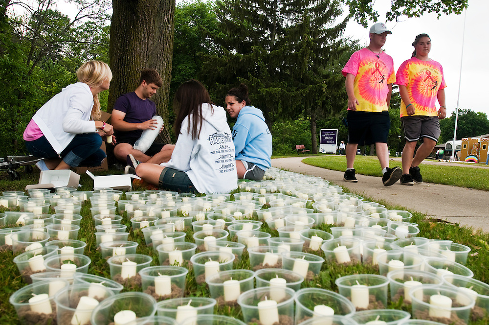 Matt Dixon   The Flint Journal..National Honor Society volunteers from flushing prepare candles for a later ceremony as other participants walk the course during the 2011 Relay For Life of Flushing Friday afternoon.