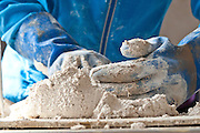 A lime plaster is being prepared to cover the walls of a strawbale building. The lime plaster helps protect the clay and straw.