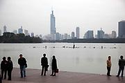 People walk near Xuanwu Lake with a view of downtown Nanjing, Jiangsu Province, China on 09 November, 2011.