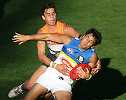 Greg Broughton of the Suns is tackled by Dylan Shiel of the Giants during the 2013 AFL round 05 match between the GWS Giants and the Gold Coast Suns at Manuka Oval, Canberra on April 27, 2013. (Photo: Craig Golding/AFL Media)
