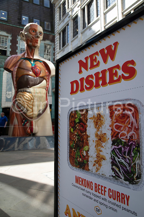 Temple by Damien Hirst sculpture has its entrails and inner organs juxtaposed with an advert for takeaway food in the City of London, England, United Kingdom. Each year, the critically acclaimed Sculpture in the City returns to the Square Mile with contemporary art works from internationally renowned artists in a public exhibition of artworks open to everyone to come and interact with and enjoy.