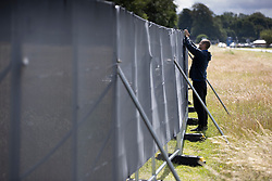 © Licensed to London News Pictures. 03/07/2020. Epsom, UK. Fences are being erected around Epsom Racecourse in Surrey ahead of the running of The Derby. Tomorrow's race meeting is being held behind closed doors due to the coronavirus lockdown rules. Seven races are being held in one day including The Oaks, with The Derby being run at 17:30pm. Photo credit: Peter Macdiarmid/LNP