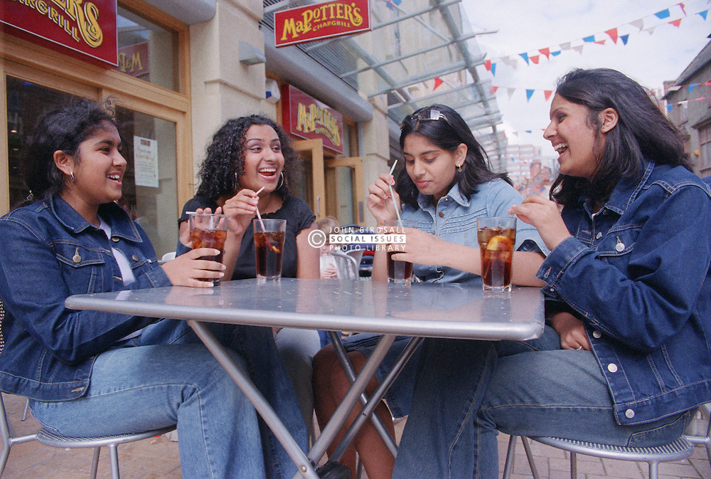 Teenage girls drinking coca cola outdoors in street café,