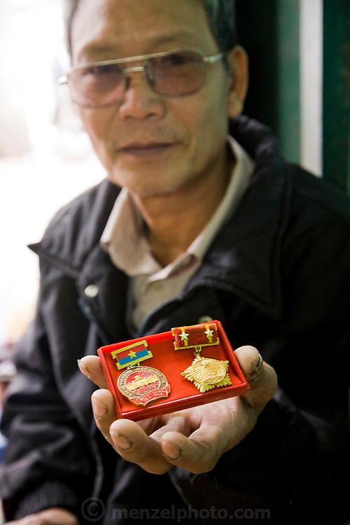Vietnamese war veteran Nguyen Van Thuan displays his medals in Hanoi, Vietnam. (Nguyen Van Thuan is featured in the book What I Eat: Around the World in 80 Diets.) MODEL RELEASED.