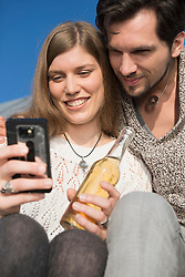 Portrait young couple cell phone SMS beer