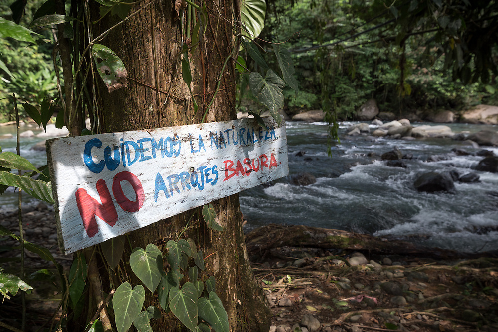 """16 November 2018, San José de León, Mutatá, Antioquia, Colombia: 'Take care of nature, do not litter,"""" a sign by the River Fortuna reads. The area of San José de León is rich in clean water - a great asset, but also a threat to the community, as mining companies and other interests may enter the scene to exploit or damage the natural resource. Following the 2016 peace treaty between FARC and the Colombian government, a group of ex-combatant families have purchased and now cultivate 36 hectares of land in the territory of San José de León, municipality of Mutatá in Antioquia, Colombia. A group of 27 families first purchased the lot of land in San José de León, moving in from nearby Córdoba to settle alongside the 50-or-so families of farmers already living in the area. Today, 50 ex-combatant families live in the emerging community, which hosts a small restaurant, various committees for community organization and development, and which cultivates the land through agriculture, poultry and fish farming. Though the community has come a long way, many challenges remain on the way towards peace and reconciliation. The two-year-old community, which does not yet have a name of its own, is located in the territory of San José de León in Urabá, northwest Colombia, a strategically important corridor for trade into Central America, with resulting drug trafficking and arms trade still keeping armed groups active in the area. Many ex-combatants face trauma and insecurity, and a lack of fulfilment by the Colombian government in transition of land ownership to FARC members makes the situation delicate. Through the project De la Guerra a la Paz ('From War to Peace'), the Evangelical Lutheran Church of Colombia accompanies three communities in the Antioquia region, offering support both to ex-combatants and to the communities they now live alongside, as they reintegrate into society. Supporting a total of more than 300 families, the project seeks to alleviate the"""