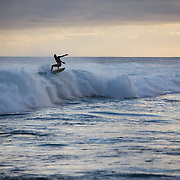 Surfing as the sun sets in Poipu on the island of Kauai.