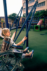Stock photo of a young girl playing on a wheel chair accessible swing
