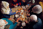 (MODEL RELEASED IMAGE). In the Golden Horn area of Istanbul, Turkey, the Çinar family gathers on the floor of their small living room to share their morning meal: feta cheese, olives, leftover chicken, bread, rose jam, and sweet, strong tea. Hungry Planet: What the World Eats (p. 10).