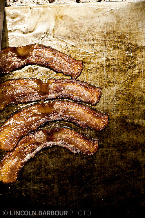 Four strips of bacon are cooked at Fuller's Diner flattop