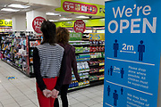 With the UK's Coronavirus pandemic lockdown easing with preparations going ahead for the opening of more public transport and services plus shops, another 151 have died from Covid-19 bringing the total in the last 24hrs to 41,279. Two customers walk past a social distancing sign at the entrance of a small supermarket in Waterloo Station, on 11th June 2020, in London, England.