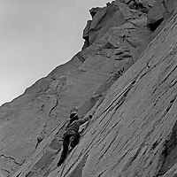"""Roger Schley ascends """"Cucumbers"""" a difficult rock climb on the north face of Cardinal Pinnacle in the Sierra Nevada above Bishop, California.  1973"""