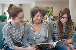 Girls reading magazine with senior woman in rest home