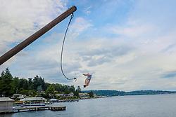 A teenage boy does a flip off of a rope into Lake Washington, near Bellevue, Washington.  MR