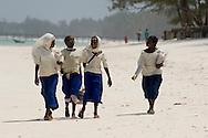 School girls walking along Kiwendwa Beach wearing white headscarves and blue skirts.  Zanzibar, Tanzania