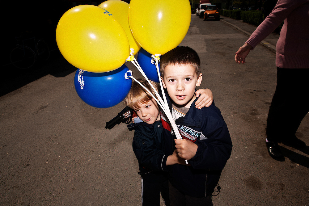 Boys playing with a toy gun and campaign balloons the central square in the Eastern Serbian town of Veliko Gradiste before President Boris Tadic arrived for a campaign event. April 19, 2012...Matt Lutton for The Wall Street Journal..SERBELECT
