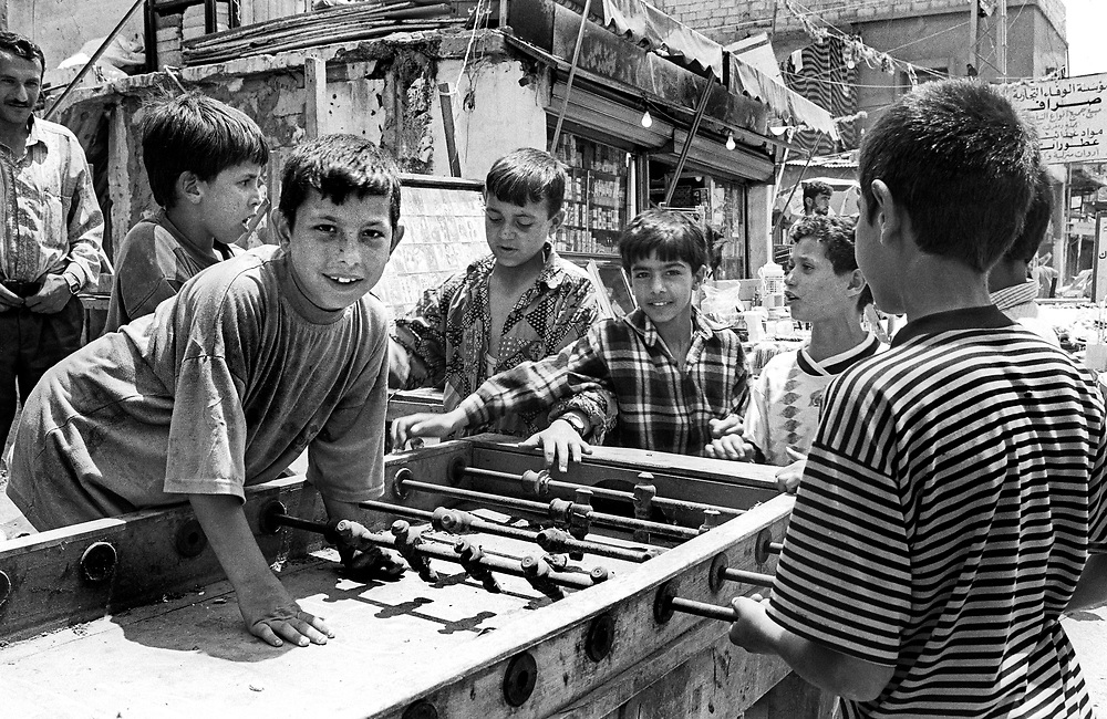 Daily life. Group of young boys playing table football in the street. Inside the Palestinian Refugee Camps of Sabra and Shatila, Beirut, Lebanon 1998.