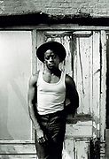 Youth wearing hat and vest, standing in front of garden shed. Photo by Richard Saunders 1983