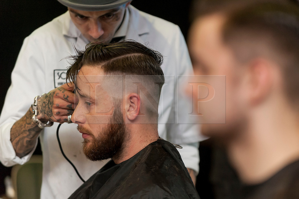 © Licensed to London News Pictures. 25/04/2016. London, UK. A barber works on a model at the Pro Hair Live event at Olympia in west London.  The show brings the latest innovation in hair care to professional hairdressers and barbers.  Photo credit : Stephen Chung/LNP