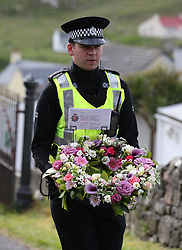 Flowers are laid by an officer from Police Scotland on behalf of the Chief Constable of Greater Manchester Police and the Mayor of Greater Manchester outside the Church of Our Lady, Star of the Sea, in Castlebay on the island of Barra, ahead of the funeral of Manchester bomb victim Eilidh MacLeod.