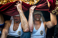 """Exhausted costaleros, the """"sack man"""" carrying the floats, take a rest and some fresh air. Each float hosts tens of them. In most Andalusia processions they walk hidden behind a velvet curtain. Seville, Spain"""