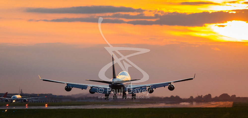 London Heathrow, September 19th 2015. As the setting sun lights up the sky in a feiry display, a Cathay Pacific Cargo Boeing 747 Freighter lands on Heathrow Airport's Runway 27R.