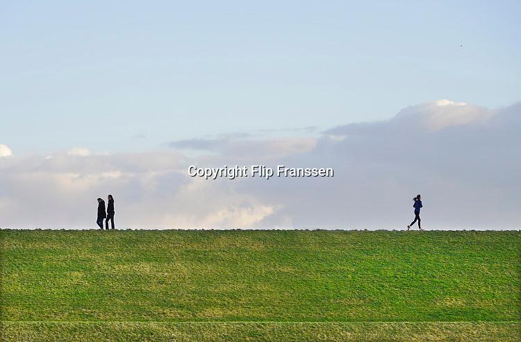 Nederland, Lent, Nijmegen, 24-2-2017Mensen wandelen en lopen hard op de dijk.Foto: Flip Franssen