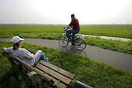 Nederland, Woerden, 3  sept 2005..Vrouw zit op een bankje te genieten van het uitzicht: Het groene hart, het open weidegebied in het centrum van Nederland, dat aan alle kanten wordt bedreigd door uitbreidingsplannen van gemeenten. Woningbouw en nieuwe industriegebieden en bedrijventerreinen bedreigen de open ruimte..Landschap.  .Foto (c) Michiel Wijnbergh