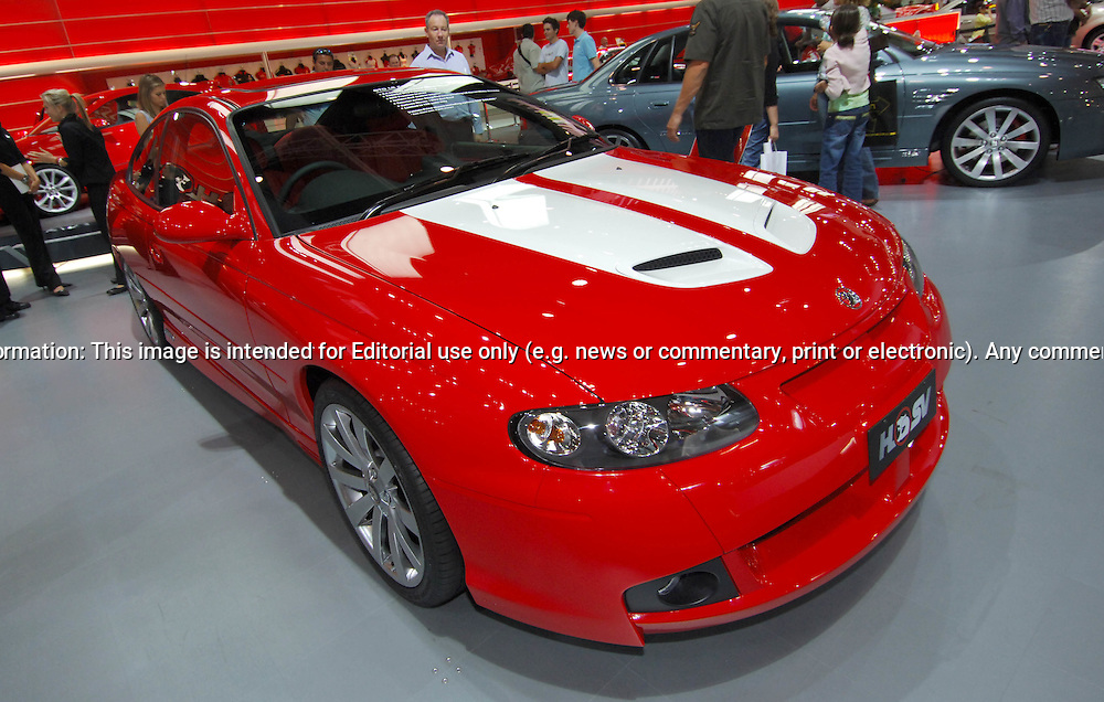 HSV LE GTO Coupé.Melbourne International Motorshow, .Melbourne Exhibition Centre. Clarendon St, Southbank, Melbourne .14th February 2006.HSV has developed a special limited edition model, the 'LE' GTO Coupé. Only 100 were built and they marked the start of the 2006 production schedule. A prerequisite for any HSV limited edition model is a distinctive standout appearance, and here the 'LE' GTO Coupé doesn't disappoint. There are three exterior colours and matching interior trim sets available, each combined with striking bonnet and boot lid paint accents. .Fifty will be built in the most conservative combination of 'Phantom Black' with 'Light Gold' accents and 'Ochre' interior trim, 25 will come in the popular 'Devil Yellow' colour with 'Black' accents and 'Devil Yellow' interior trim, while the remaining 25 will be available in HSV's classic 'Sting Red' paintwork with White accents and Indiana (Red) interior trim..Further enhancements to the car's bold street presence can be found in special badges and black brake callipers, the limited edition HSV build number painted on the boot lid in the same colour, as well as HSV 10-spoke 19-inch alloy wheels (Light Gold on Black cars and Chrome Shadow with the other combinations). There is also an individual rear profile for LE with the deletion of the usual GTO rear spoiler, and the addition of a roof spoiler..Interior Enhancements will also include Premium dashboard highlights and Bluetooth. Braking is upgraded to an AP Racing 4 Piston Premium System..The limited edition LE GTO Coupé shares the remainder of its awesome specification with the regular Coupe GTO model, including the exclusive to HSV, 6.0 litre LS2 V8 which produces an extraordinary 297kW @ 6000rpm and 530Nm @ 4400rpm and will accelerate to 100kmh in just over 5 seconds..(C) Joel Strickland Photographics.Use information: This image is intended for Editorial use only (e.g. news or commentary, print or electronic). Any commercial or promotional use requires addit